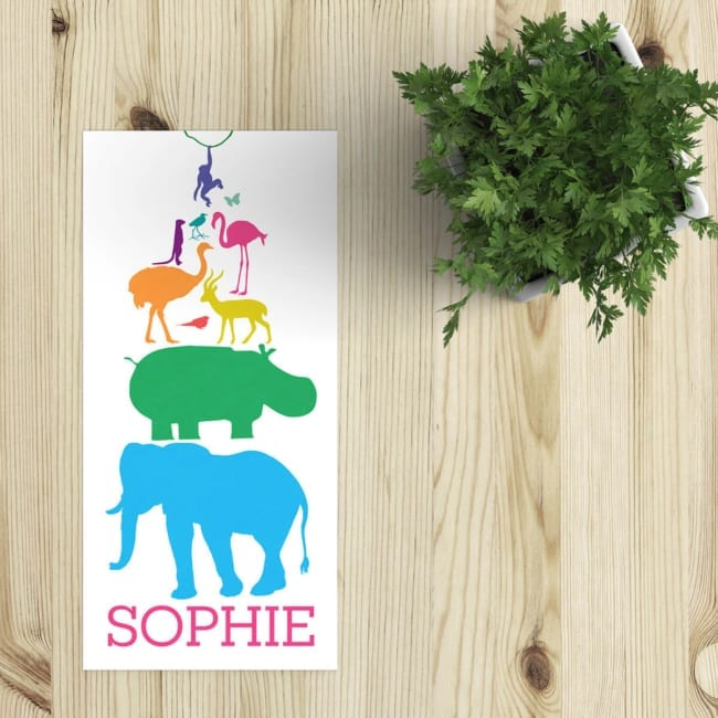 """Kleurrijk, vrolijk en bovenal """"dierlijk,"""" geboortekaartje Dieren Feest is een feestje van dieren, geïllustreerd in een minimalistische, silhouet stijl. Afbeelding toont voorkant van geboortekaart op houten tafel."""
