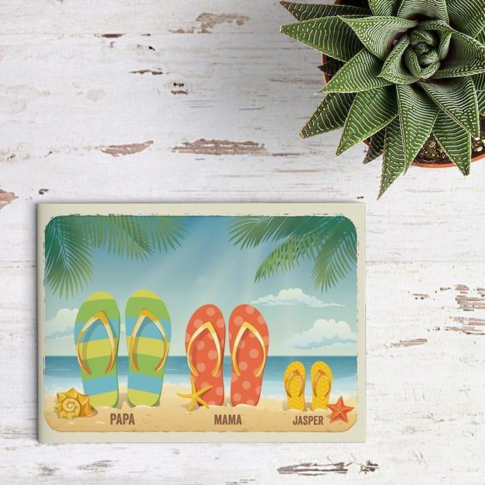 Geboortekaartje Baby Slippers is grappig kaartje: een nieuw setje slippers wordt toegevoegd aan het gezin. Op het strand staat een extra setje in het zand.